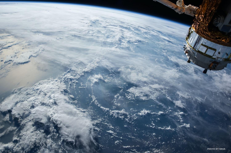 Widok z kosmosu na Ziemię spowitą chmurami. W prawym górnym rogu widoczny fragment wehikułu
