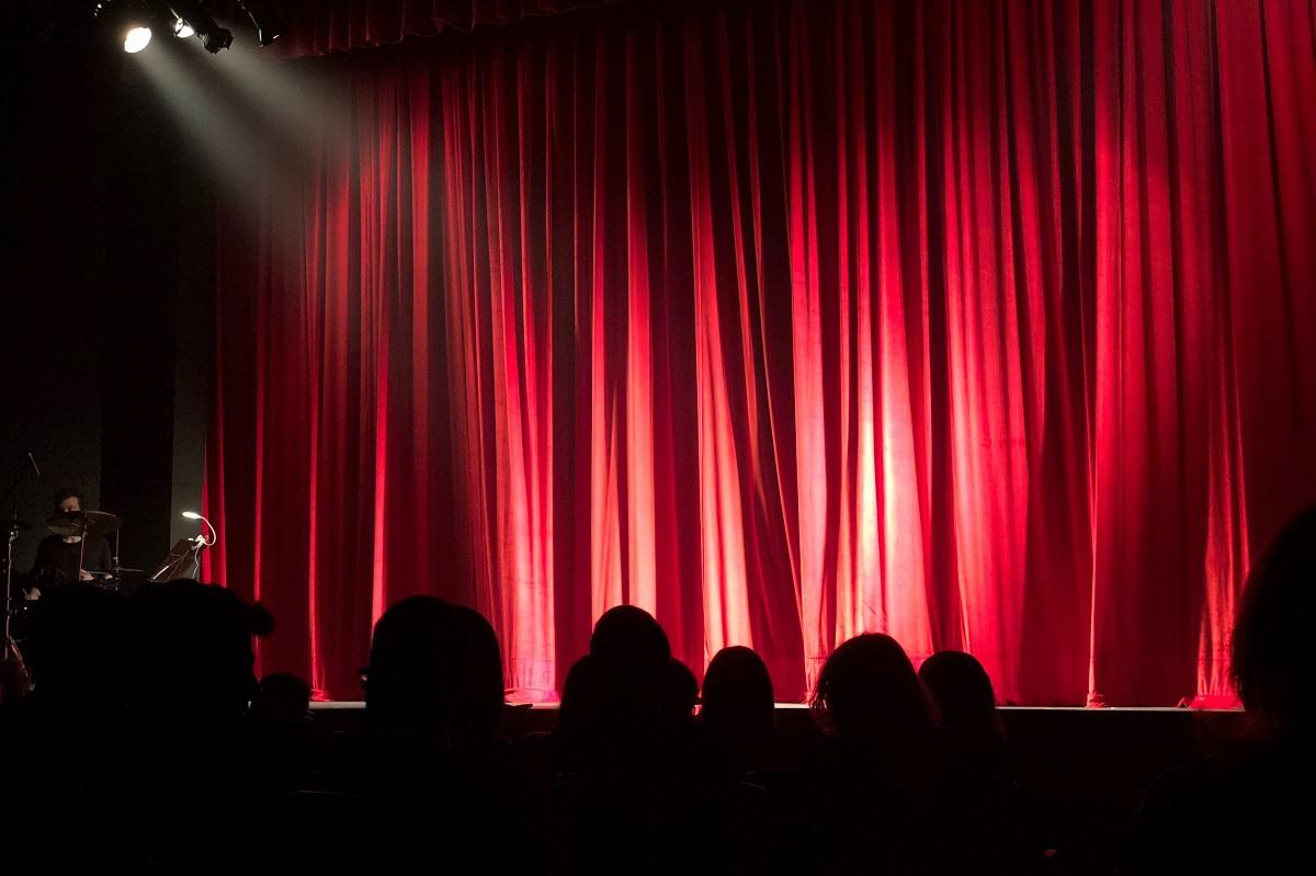 Widok na scenę zasłoniętą czerwoną kurtyną i oświetloną reflektorem. Na pierwszym planie widać pogrążone w cieniu głowy widzów